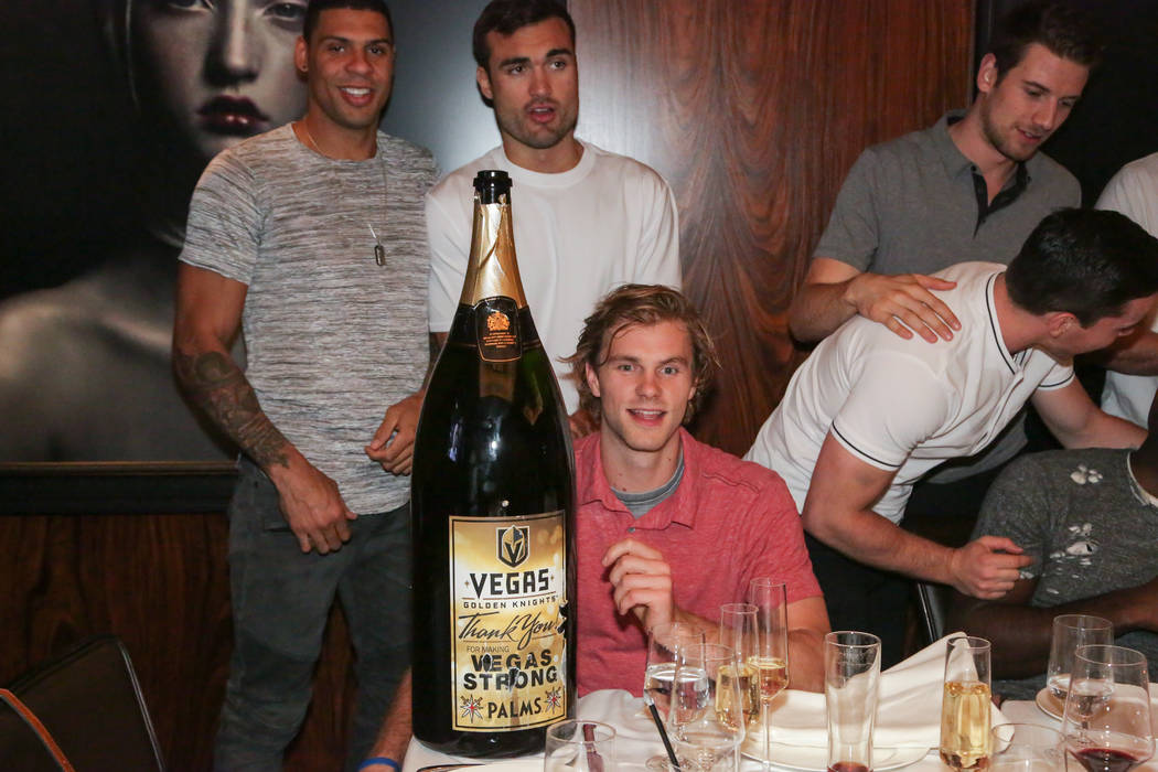 Members of the Vegas Golden Knights, clockwise from upper left, Ryan Reaves, Will Carrier, Jonathan Maechessault (looking away), Shea Theodore and Jon Merrill (seated) are shown with a 15-liter bo ...