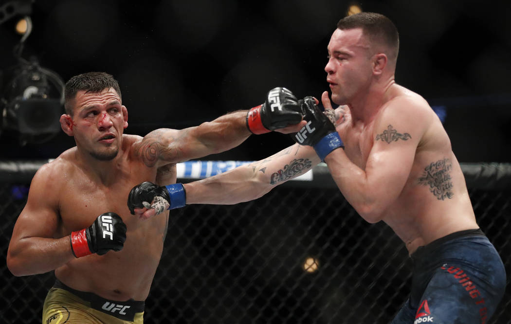 Rafael Dos Anjos, left, and Colby Covington exchange punches during their interim welterweight UFC 225 mixed martial arts bout Saturday, June 9, 2018, in Chicago. (AP Photo/Jim Young)