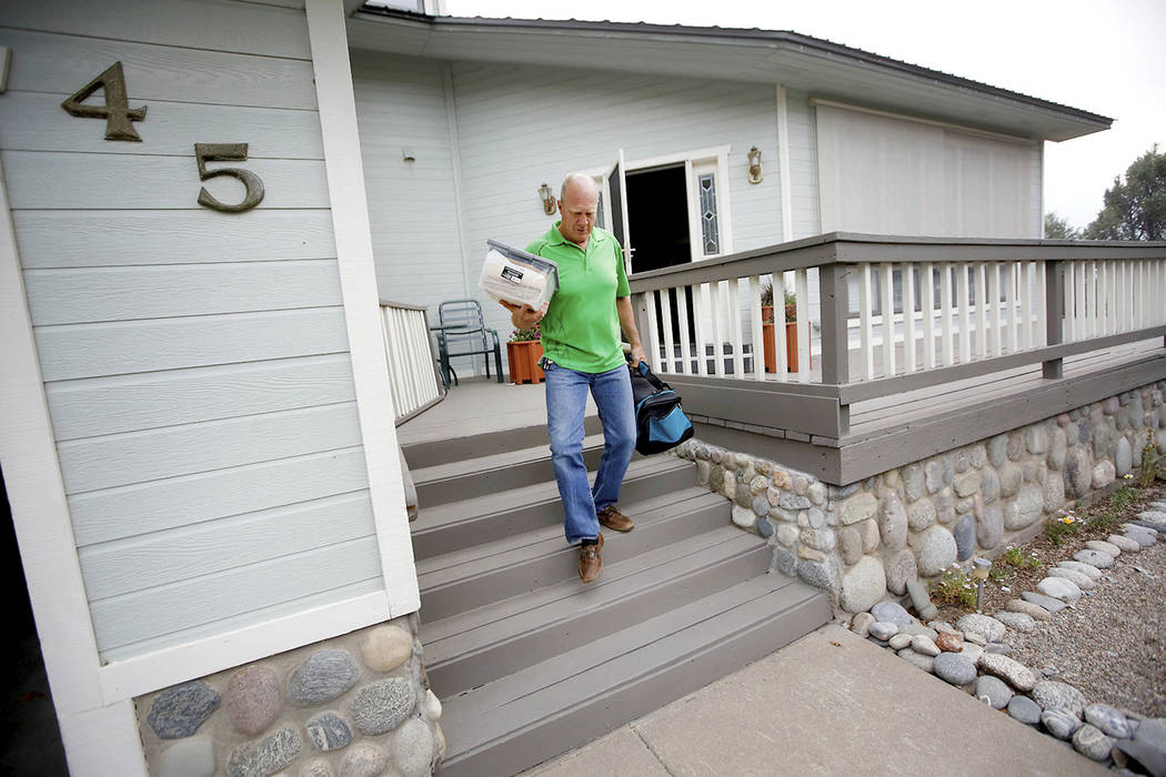Tim Sparks carries items out of his home near Hermosa, Colo., on County Road 201 on Thursday, June 7, 2018, to load in his truck as he evacuates the area. (Jerry McBride/Durango Hearld via AP)