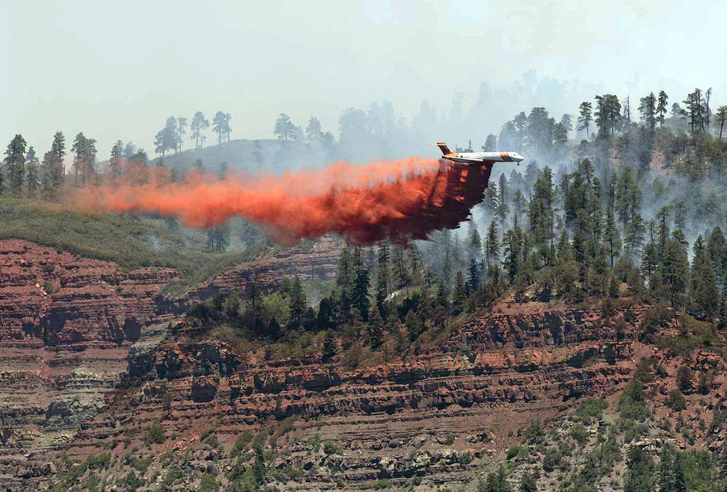 An aircraft makes a fire retardant drop on a wildfire in the hills and forests near Durango, Colo., Friday, June 8, 2018. (Jerry Day via AP)