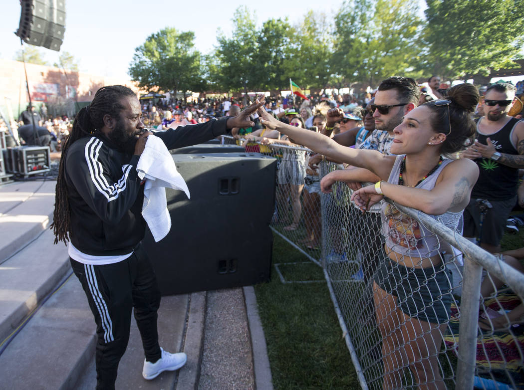 Jamaican singer Prestige, left, locks hands with Victoria Agramonte of San Francisco, Calif., while performing during Reggae in the Desert at the Clark County Amphitheater in downtown Las Vegas on ...