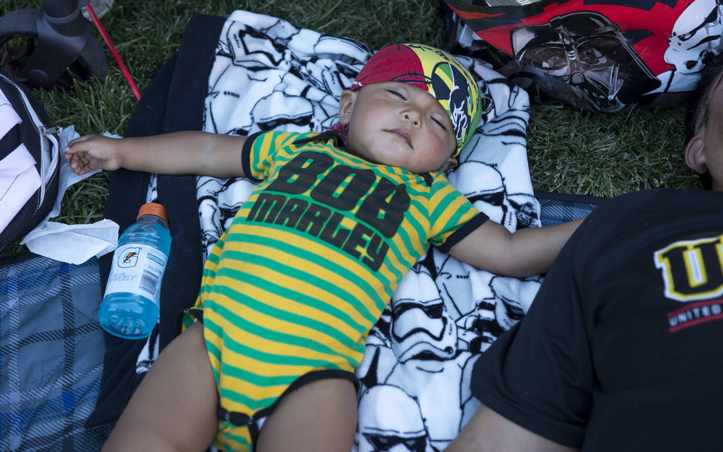 18-month-old Home'e Uqualla takes a nap next to his dad during Reggae in the Desert at the Clark County Amphitheater in downtown Las Vegas on Saturday, June 9, 2018. Richard Brian Las Vegas Review ...