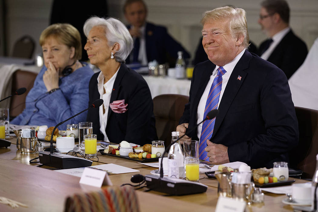 President Donald Trump smiles as he arrives for the Gender Equality Advisory Council breakfast during the G-7 summit, Saturday, June 9, 2018, in Charlevoix, Canada. From left, German Chancellor An ...