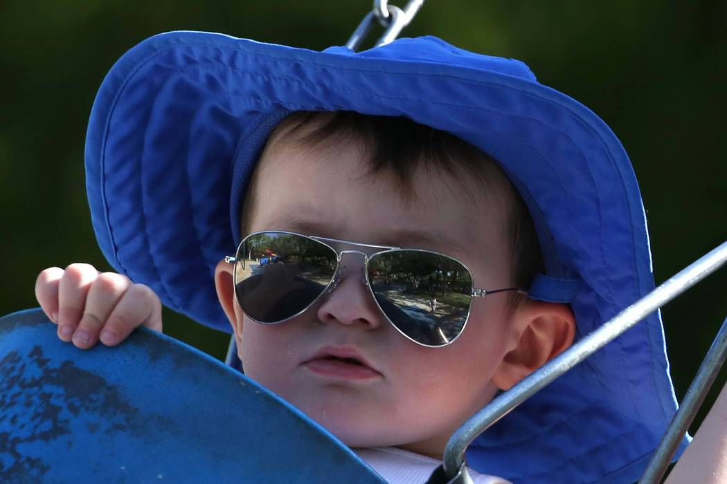 Two-year-old Jason wears a large hat and sunglasses to protect himself from the sunlight while on a swing at Discovery Park on Monday, June 4, 2018, in Henderson. (Bizuayehu Tesfaye/Las Vegas Revi ...