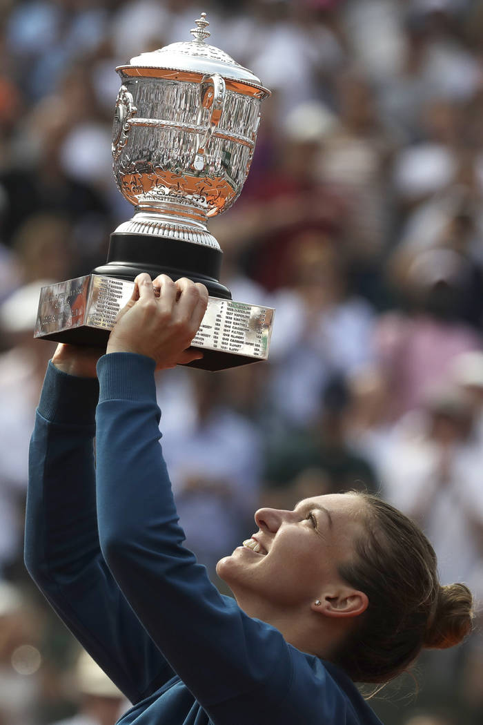 Romania's Simona Halep raises the trophy as she celebrates winning the final match of the French Open tennis tournament against Sloane Stephens of the U.S. in three sets 3-6, 6-4, 6-1, at the Rola ...