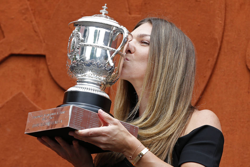 Romania's Simona Halep kisses with the cup at the Roland Garros stadium, Sunday, June 10, 2018 in Paris. Halep won Saturday the French Open tennis tournament women's final. (AP Photo/Thibault Camus)