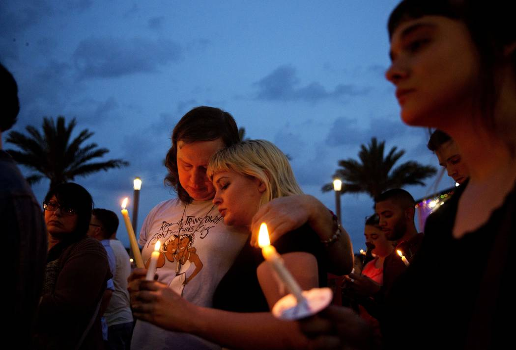 FILE - In this June 13, 2016, file photo, Lucinda Rex, right, and Clarity Thorne embrace during a candlelight vigil downtown for the victims of a mass shooting at the Pulse nightclub in Orlando, F ...
