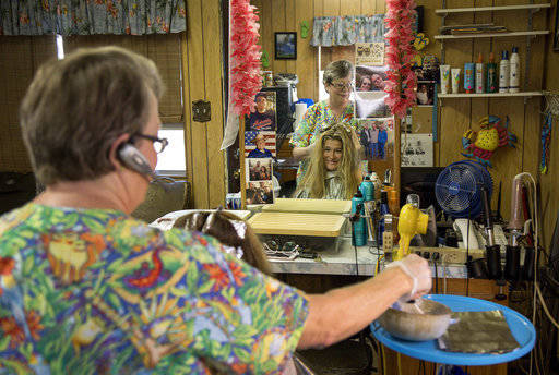 In this Thursday, May 17, 2018 photo, Sydney TenCate, who graduated from Moran High School, gets her hair done by, Cynthia Gilmore, owner of His & Hers Hair Styling, one of the few businesses ...