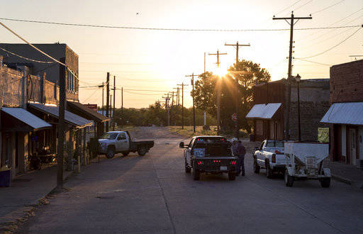 In this Thursday, May 17, 2018 photo, the sun rises over downtown Moran, Texas as a handful of people gather for breakfast at the town's only restaurant. Moran is like anywhere else in rural Texa ...