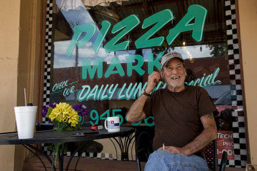 In this Wednesday, May 16, 2018 photo, Carlton Edgar drinks coffee at Pizza Mark, the town's only restaurant in Moran, Texas. The town's downtown area has few remaining businesses, and the town la ...