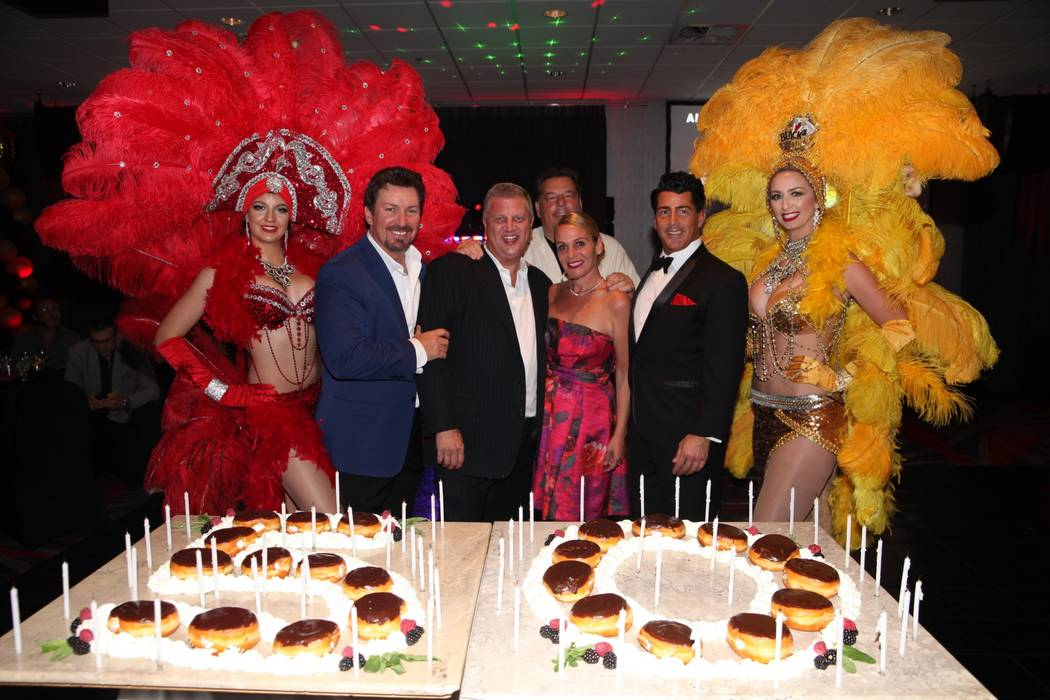 Flanked by showgirl models, Richard Wilk, The D Las Vegas co-owner Derek Stevens; Stevens' wife, Nicole; Vincent Pastore; Steve Schirripa; and Drew Anthony (as Dean Martin) are shown at Wilk's 50t ...