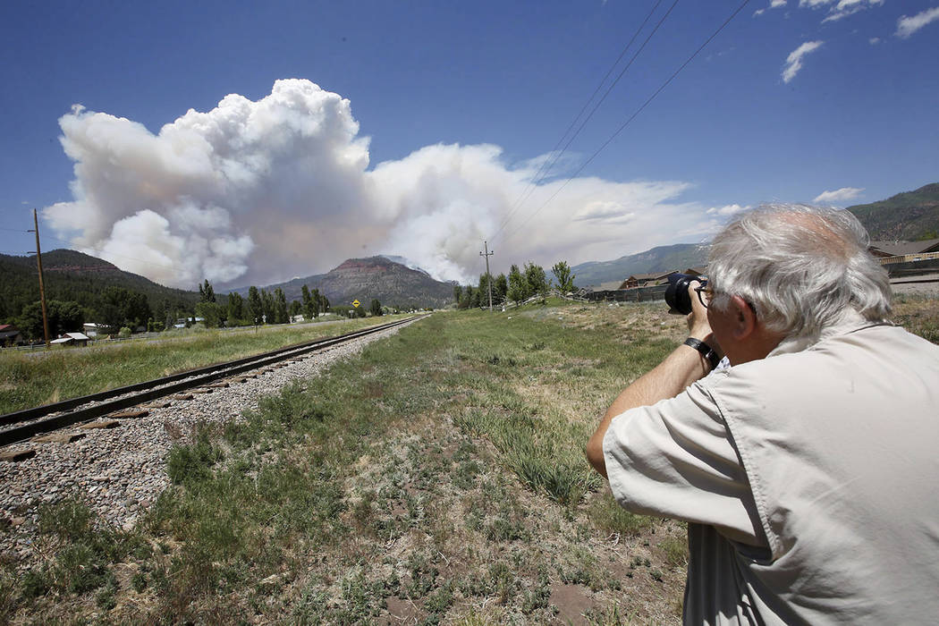 In this Saturday, June 9, 2018 photo, Paul Boyer of Durango, Colo., levels his camera for a shot of the plume as it rises from the wildfire near Hermosa, Colo. (Jerry McBride/The Durango Herald v ...