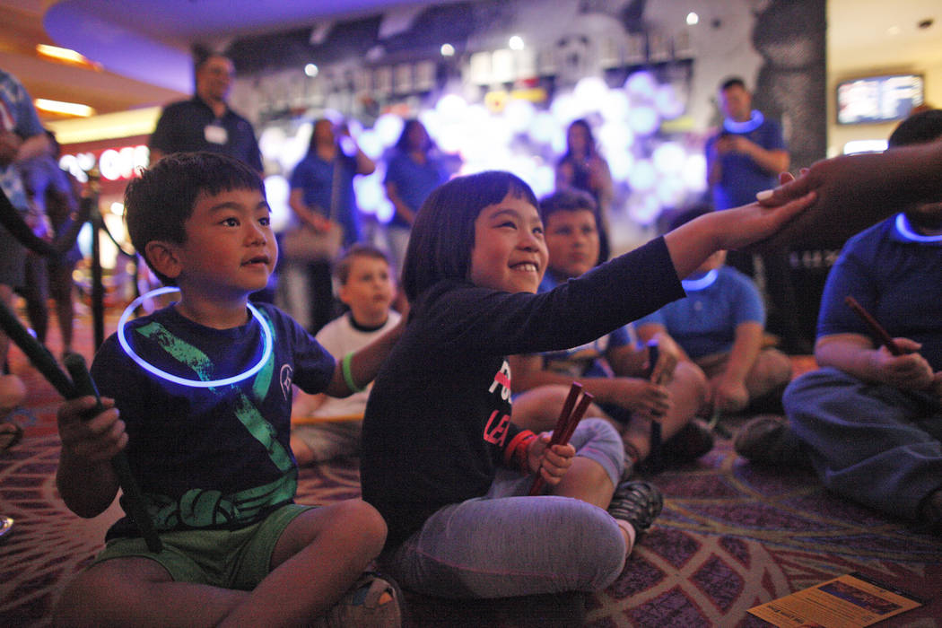 Analu Tam, 6, left, watches as his sister Kailana Tam, 9, grabs the hand of teacher Linda Austin during a drum circle activity at the Luxor hotel-casino in Las Vegas, Sunday, June 10, 2018. The ev ...