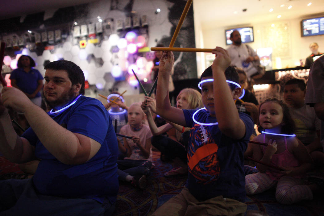 Joseph Giannotta, 19, left, plays along in a drum circle with Leo Murphy, 11, at the Luxor hotel-casino in Las Vegas, Sunday, June 10, 2018. The event took place before the Blue Man Groups' Grant ...