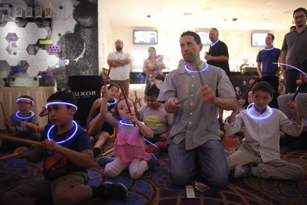 Leo Murphy, 10, from left, Hailey Martin, 4, her father Sergio Martin, and her brother Esteban Martin, 9, participate in a drum circle outside the Blue Man Group show at the Luxor hotel-casino in ...