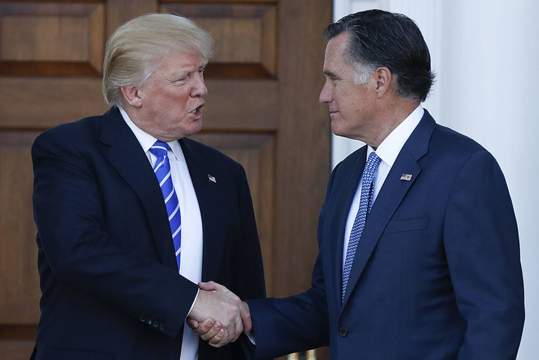 Donald Trump and Mitt Romney shake hands as Romney leaves Trump National Golf Club Bedminster in Bedminster, N.J., in November 2016. (AP Photo/Carolyn Kaster)