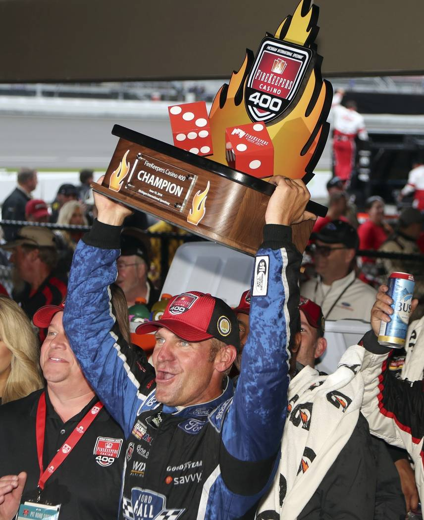 Clint Bowyer holds the Firekeepers Casino 400 trophy after winning a shortened NASCAR Cup Series auto race, Sunday, June 10, 2018, in Brooklyn, Mich. (AP Photo/Carlos Osorio)