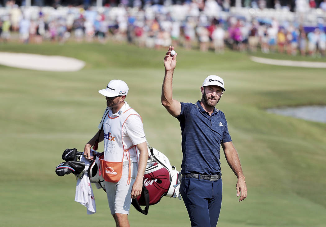 Dustin Johnson waves to the crowd after an eagle on the 18th hole during the final round of the St. Jude Classic golf tournament Sunday, June 10, 2018, in Memphis, Tenn. (Jim Weber/The Commercial ...
