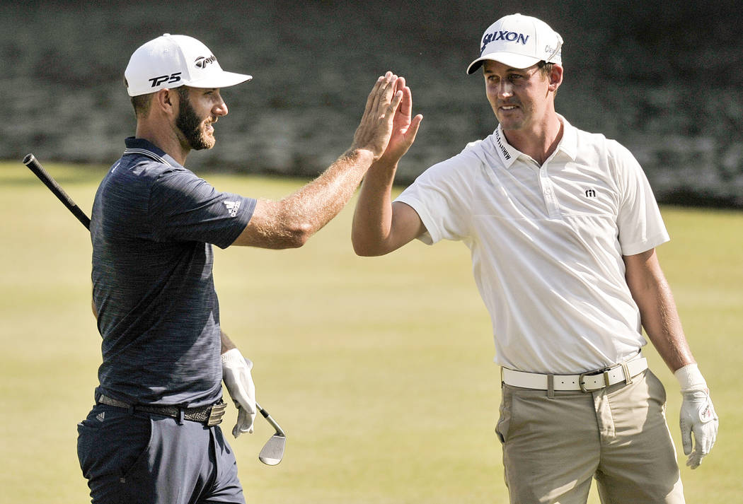 Dustin Johnson, left, is congratulated by playing partner Andrew Putnam after Johnson won the St. Jude Classic golf tournament Sunday, June 10, 2018, in Memphis, Tenn. Johnson won the tournament a ...