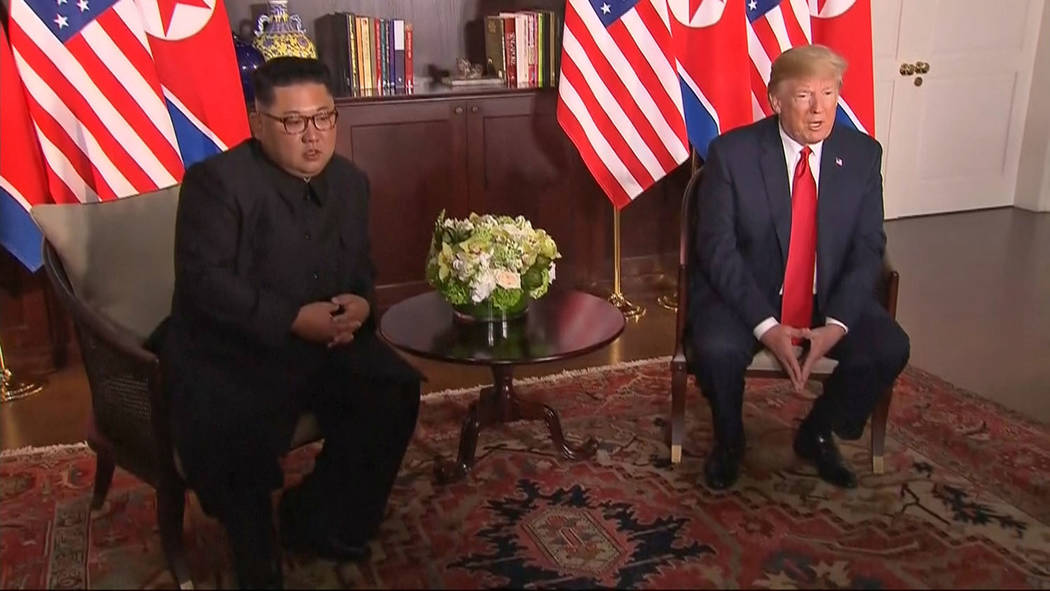 In this image made from video provided by Host Broadcaster Mediacorp Pte Ltd,, U.S. President Donald Trump and North Korean leader Kim Jong Un sit together for their meeting at Capella Hotel in Si ...