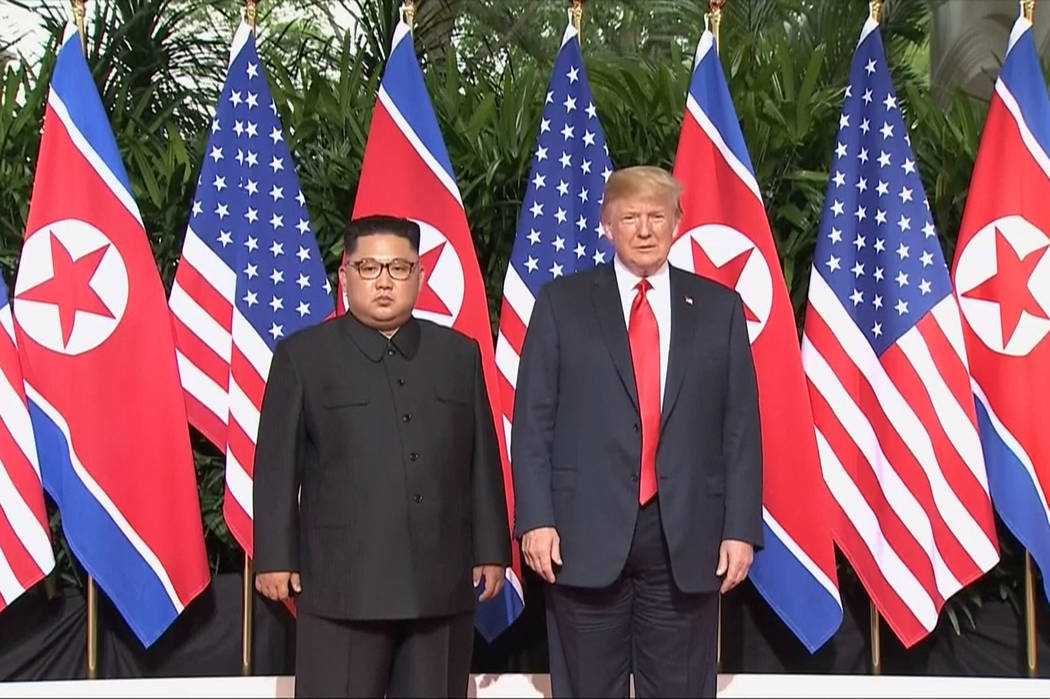 In this image made from video provided by Host Broadcaster Mediacorp Pte Ltd., U.S. President Donald Trump and North Korean leader Kim Jong Un pose together ahead of their meeting at Capella Hotel ...