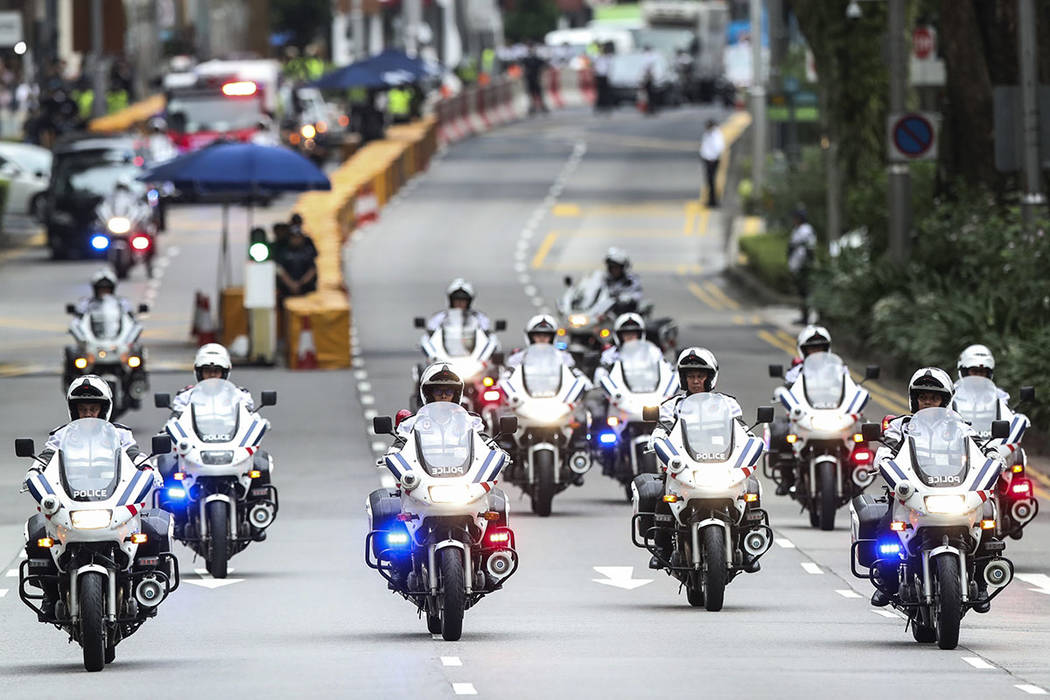 Police officers lead a motorcade of North Korean leader Kim Jong Un as they leave the St. Regis Hotel on the way to the Capella Hotel in Singapore, Tuesday, June 12, 2018, where the summit between ...