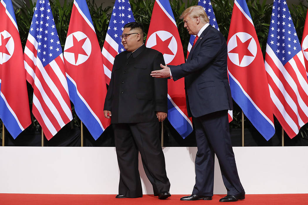 U. S. President Donald Trump guides North Korea leader Kim Jong Un toward their bi-lat meeting site at the Capella resort on Sentosa Island Tuesday, June 12, 2018 in Singapore. (AP Photo/Evan Vucci)