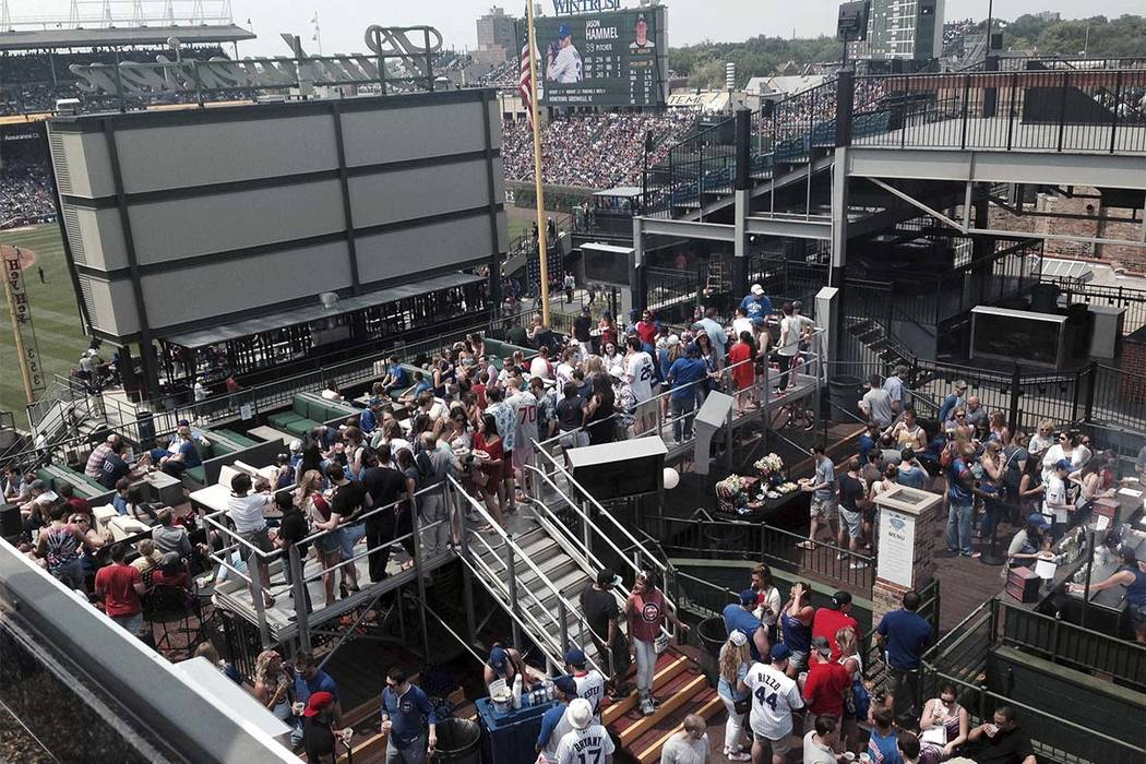 In this July 3, 2015, photo, fans watch what they can of a baseball game between the Miami Marlins and the Chicago Cubs on a rooftop across the street from Wrigley Field in Chicago. (Andrew Selig ...