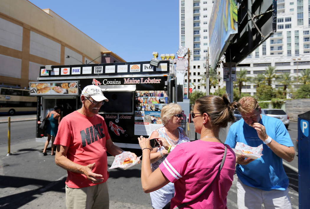 Bill and Kathy Forbes, left, and Kevin and Kristen Clark of Stamford, Conn. share lobster rolls from Cousins Maine Lobster food trailer on the corner of Fremont Street and Las Vegas Boulevard in d ...