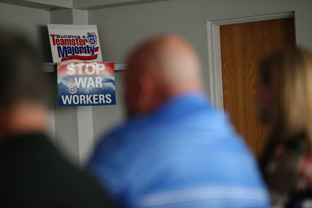 Posters in the background as people attend a watch party of the state Supreme Court hearing involving Teamsters Local 14 to determine who represents support staff, at the Teamsters Local 14 headqu ...