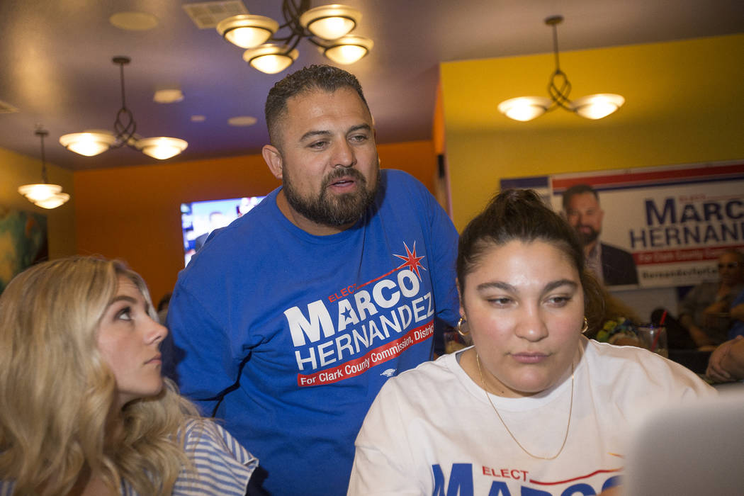 Kayla Paul, from left, Marco Hernandez, who is running for Clark County Commission District E, and Aida Blankenship look over the newest results in his race against Sen. Tick Segerblom, (D-Las Veg ...