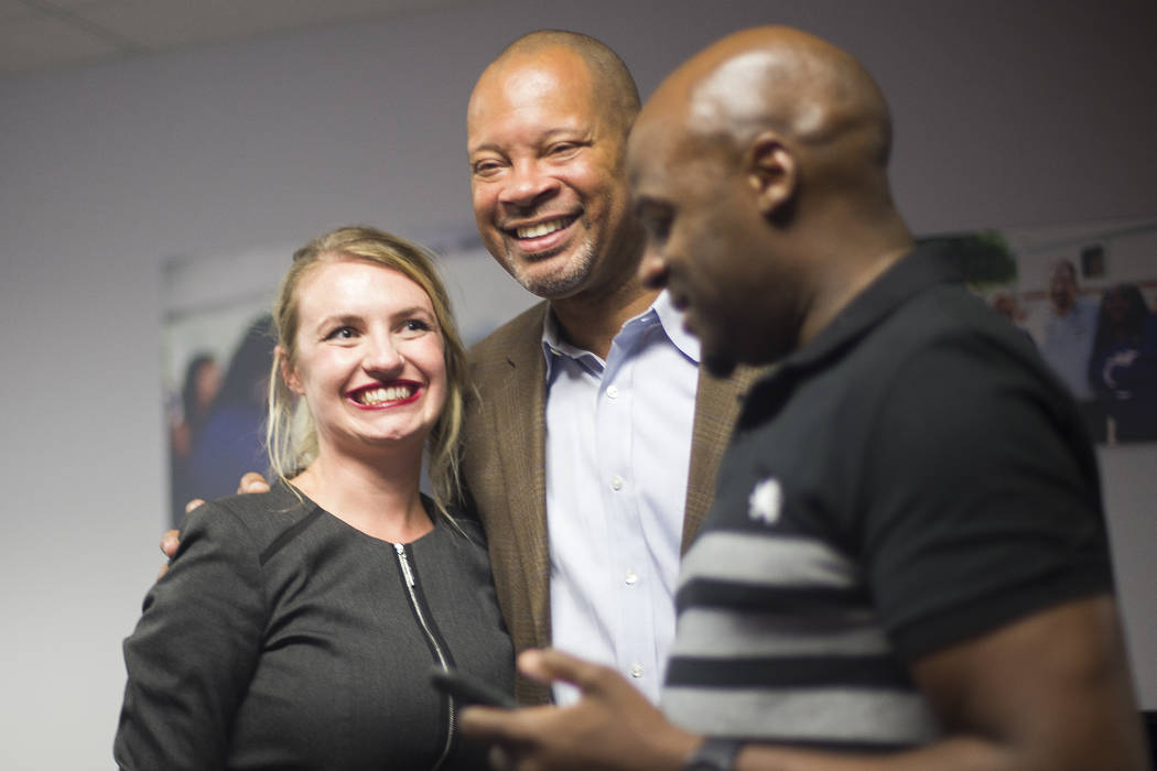 Melanie Scheible, a Democrat running for state Senate District 9, hugs Senate Majority Leader Aaron Ford, D-Las Vegas who is running for Attorney General, next to Sen. Kelvin Atkinson, (D-North La ...