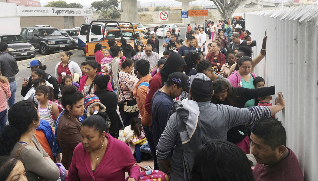 FILE - In this Monday, June 4, 2018 file photo, people seeking political asylum in the United States line up to be interviewed in Tijuana, Mexico, just across the U.S. border south of San Diego. I ...