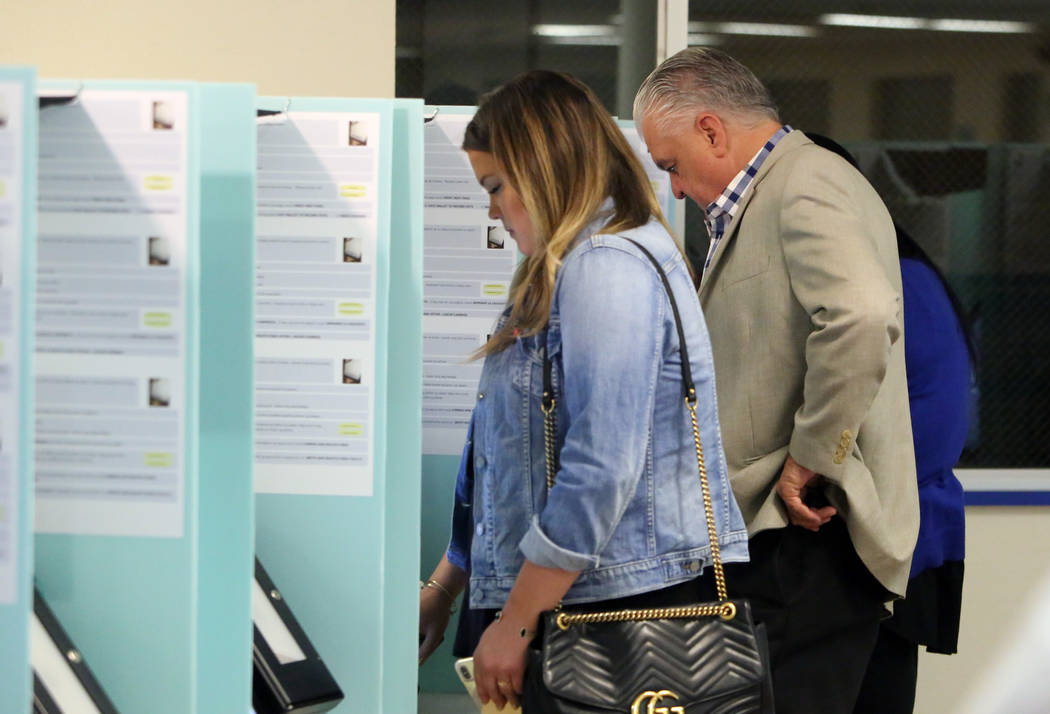 Clark County Commission Chairman and Democratic gubernatorial candidate Steve Sisolak, right, and his daughter Carley cast their vote at a polling station at Kenny G. Guin Middle School on Tuesday ...