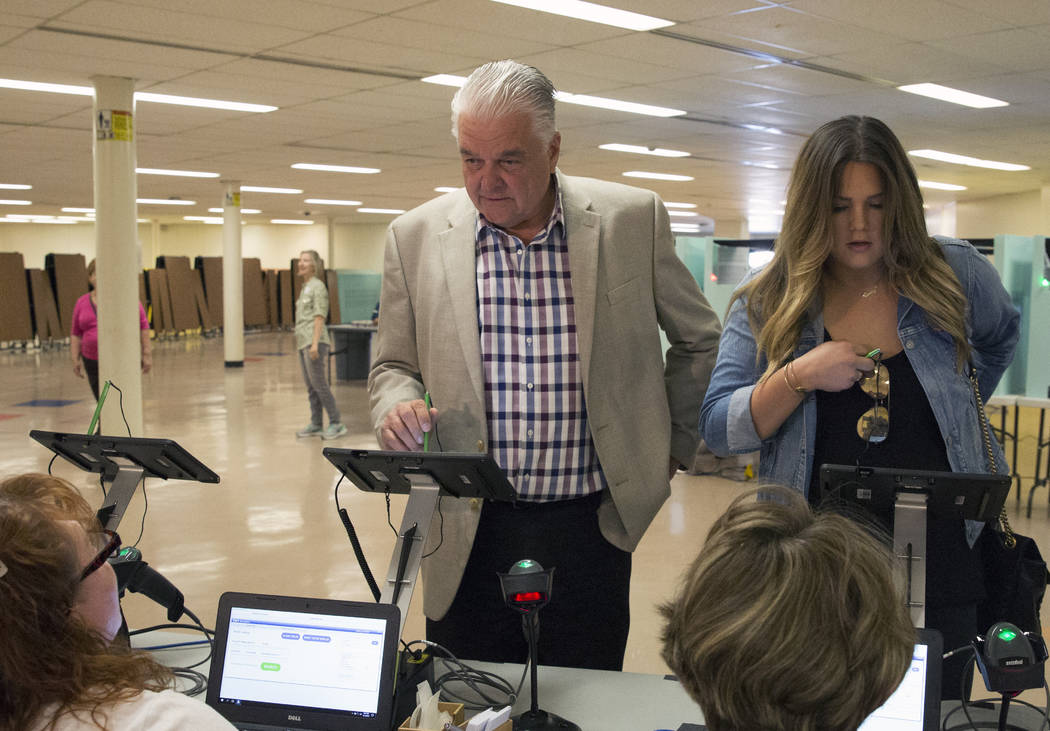 Clark County Commission Chairman and Democratic gubernatorial candidate Steve Sisolak, left, and his daughter Carley check in at a polling station at Kenny G. Guin Middle School to cast their vote ...