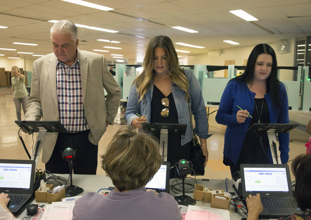 Clark County Commission Chairman and Democratic gubernatorial candidate Steve Sisolak, left, and his daughters Carley and Ashley check in at a polling station at Kenny G. Guin Middle School to cas ...