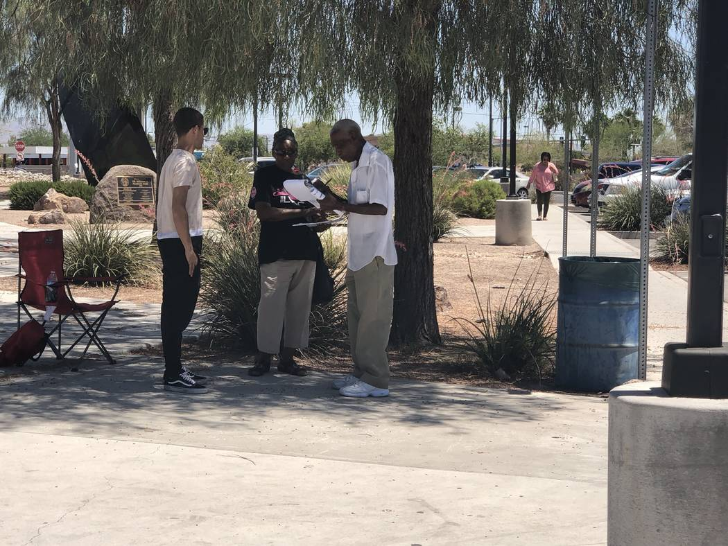Delores Millner, center, waits as her husband, Robert Millner, left, signs a petition after they voted in the primary election at Dr. William U. Pearson Community Center in North Las Vegas, Tuesda ...