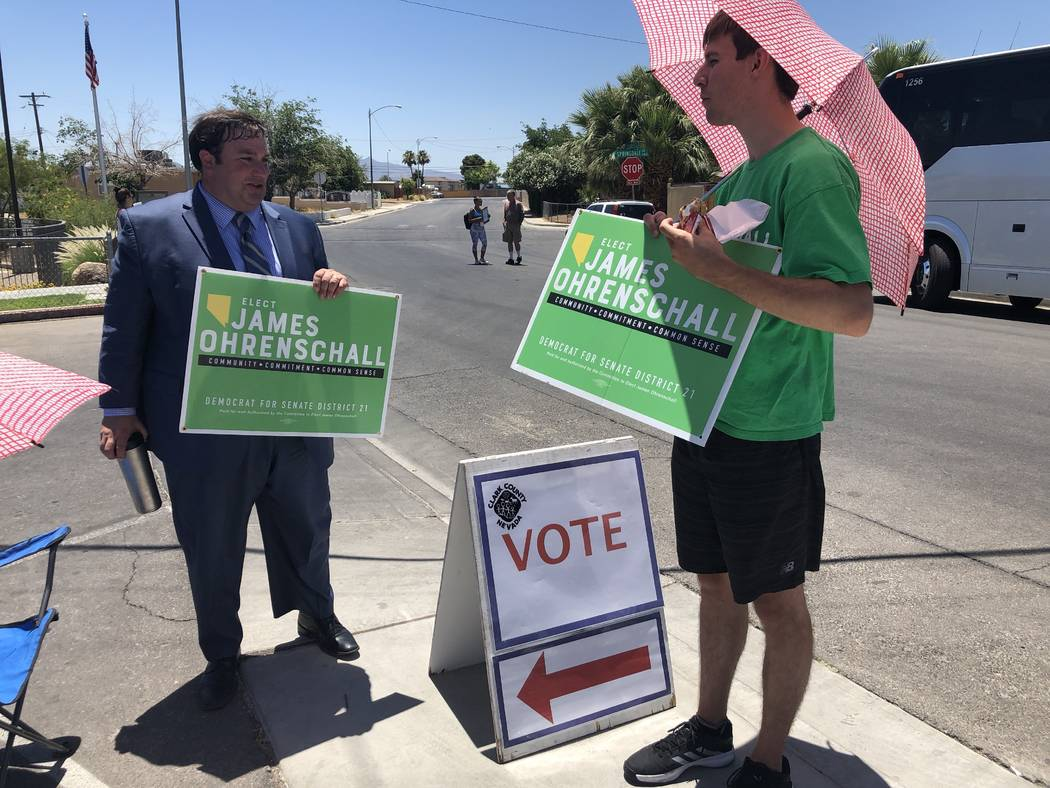James Ohrenschall, left, a Democrat running for state Senate for District 12, and volunteer Adam Forbes campaign outside Parkdale Community Center in Las Vegas on primary election day, Tuesday, Ju ...