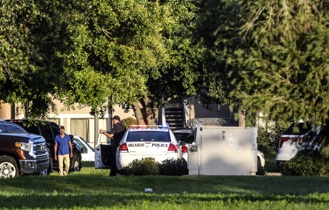 Police continue to work at the scene of a hostage standoff where a police officer was shot Monday morning, June 11, 2018, in Orlando. Police said a man suspected of battering his girlfriend wounde ...