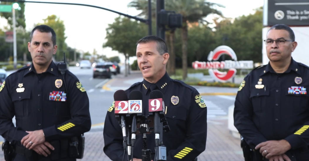 In this image made from video, Orlando Police Chief John Mina, center, speaks during a news conference, Monday, June 11, 2018, during a hostage standoff where a police officer was shot in Orlando, ...