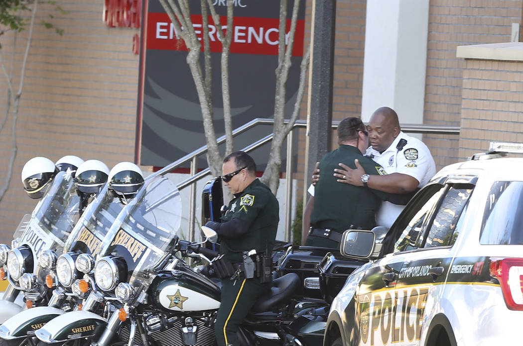 A Orange County Sheriff Motor deputy,center, gives support to a Orlando Police Motor officer,right, at Orlando Regional Medical Center after a OPD officer was shot and severely injured while respo ...