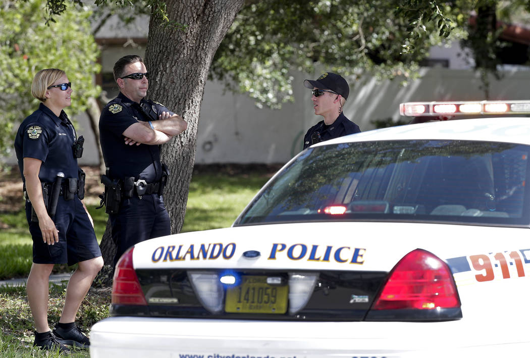 Orlando Police block an intersection leading to an apartment complex where an officer was shot and seriously wounded before the gunman barricaded himself in an apartment with young children. Monda ...