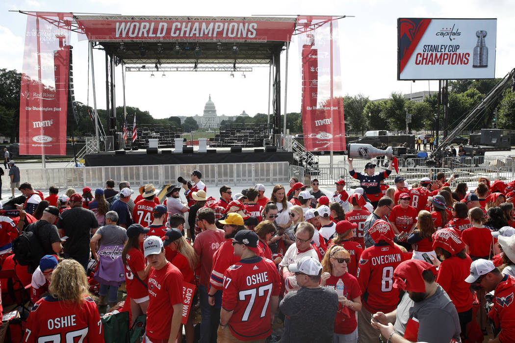 With the U.S. Capitol in the background, hockey fans gather on the National Mall ahead of a victory parade and rally for the Washington Capitals in celebration of winning the Stanley Cup, Tuesday, ...