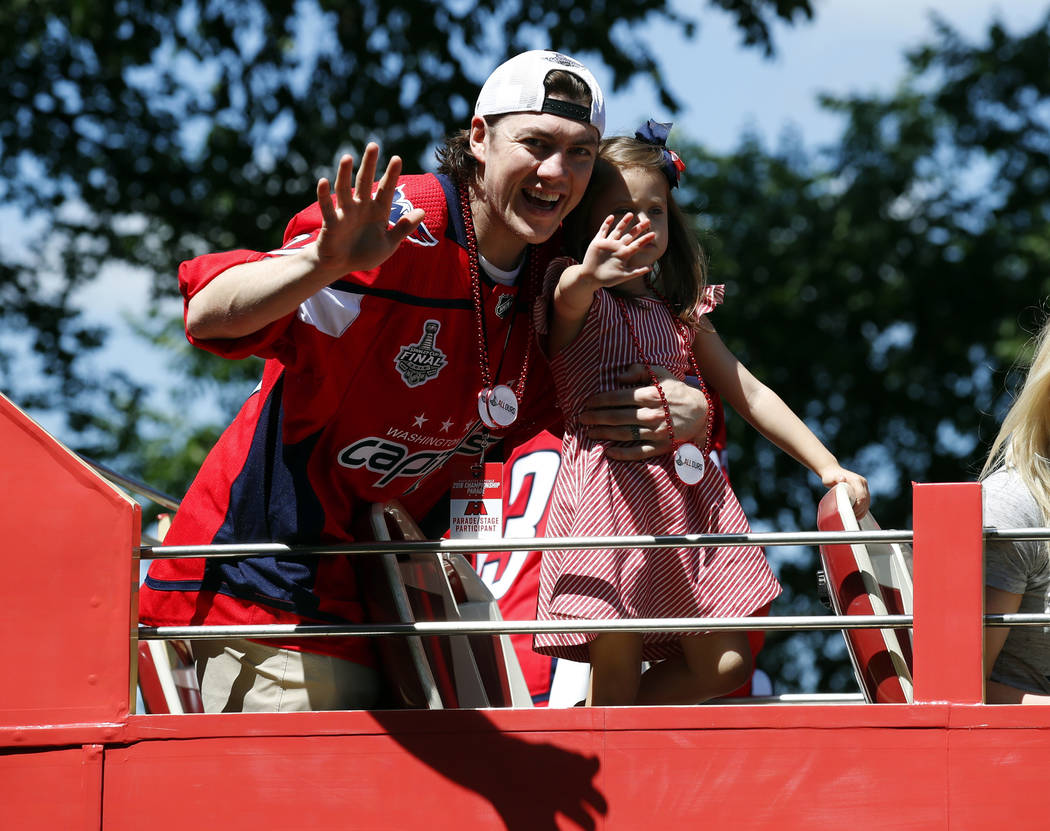 Washington Capitals right wing T.J. Oshie waves while holding his daughter Lyla Oshie during a Stanley Cup NHL hockey victory parade, Tuesday, June 12, 2018, in Washington. (AP Photo/Alex Brandon, ...