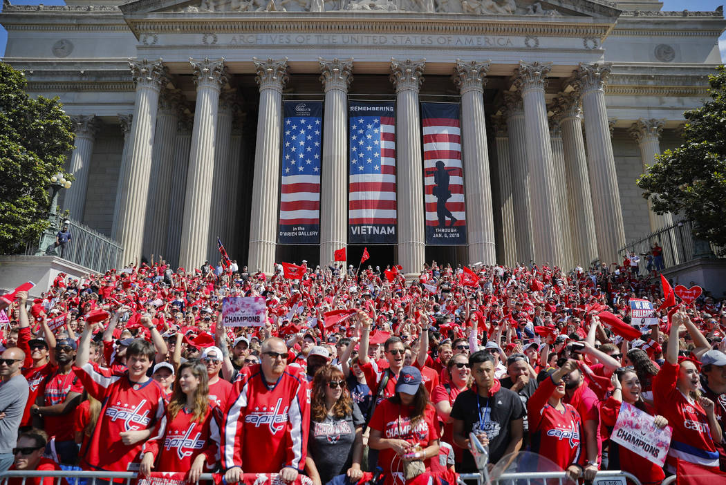 Fans gather on the steps of the National Archives Building as they wait to watch the Washington Capitals NHL hockey Stanley Cup victory parade along the National Mall in Washington, Tuesday, June ...