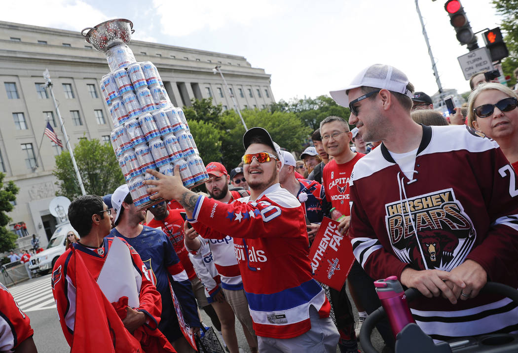 A fan carries a home-made Stanley Cup made of mostly empty beer cans as people begin to arrive for the Washington Capitals Stanley Cup victory parade on Constitution Ave., along the National Mall ...