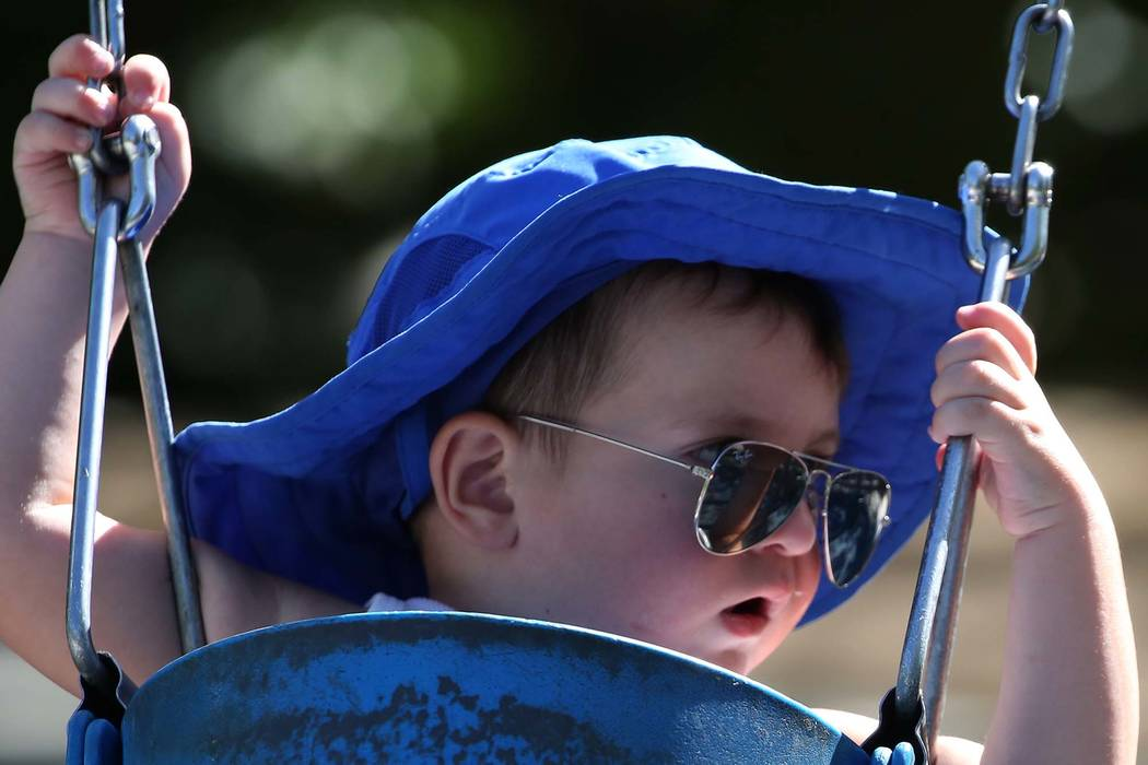 Two-year-old Jason wears a large hat and sunglasses to protect himself from the sun as he plays on a swing at Discovery Park in Henderson. (Bizuayehu Tesfaye/Las Vegas Review-Journal) @bizutesfaye