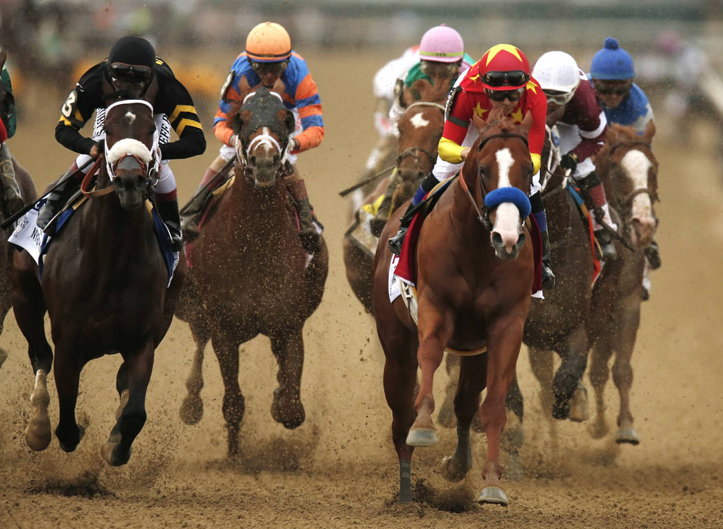 Justify (1), with jockey Mike Smith up, leads the pack as it approaches the first turn during the 150th running of the Belmont Stakes horse race, Saturday, June 9, 2018, in Elmont, N.Y. (AP Photo/ ...