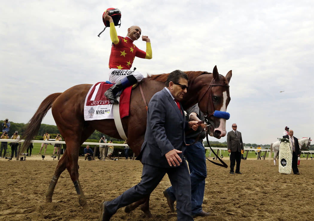 Assistant trainer Jimmy Barnes leads Justify to the winner's circle as jockey Mike Smith celebrates after winning the Triple Crown at the150th running of the Belmont Stakes horse race, Saturday, J ...