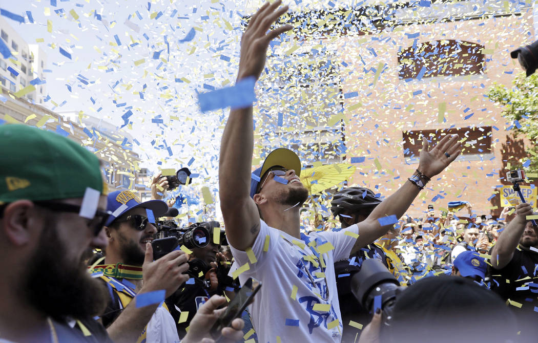 Golden State Warriors' Stephen Curry celebrates as confetti comes down during the team's NBA basketball championship parade, Tuesday, June 12, 2018, in Oakland, Calif. (AP Photo/Marcio Jose Sanchez)